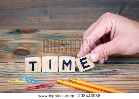 Time. Wooden letters on the office desk. Business and money investment background.