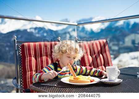 Child Eating Apres Ski Lunch. Winter Snow Fun For Kids.