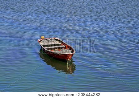 A red fishing boat is anchored in the water near a rocky shoreline.