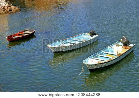 Three fishing boats are anchored in the water near a rocky shoreline.