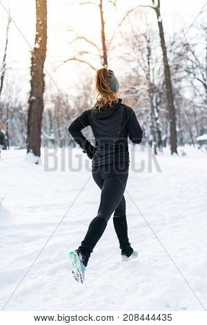 Female Athlete Jogging In Park In Winter, Color Image