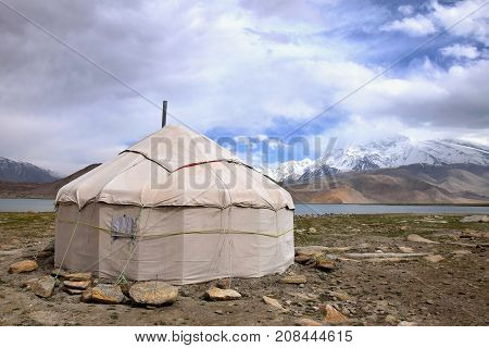 The yurt in front of Karakul Lake in Xinjiang Uighur Autonomous Region of China with Muztagh Ata hill, the second highest of the Kunlun mountains, in the background.