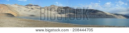 Karakul Lake and its famous landscape in Xinjiang Uighur Autonomous Region of China is the highest lake of the Pamir plateau, near the junction of the Pamir, Tian Shan and Kunlun mountain ranges.