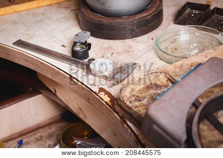 Close-up picture of retro tools for jewelry accessory crafting on a workshop table background. Goldsmith equipment for jewelry production.