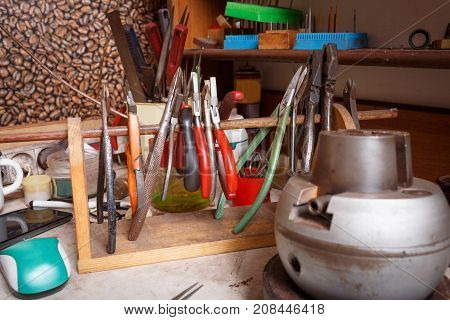 Close-up picture of different crafting tools on a workshop table background. Handmade classic craft jewelry making on vintage equipment.