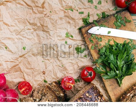 Kitchen background with baking paper tomatoes radish and parsley