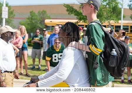 Green Bay WI - August 1 2017: Green Bay Packer Davante Adams rides a young fans bike after football practice. The community owned team has a long tradition of player involvement with fans.