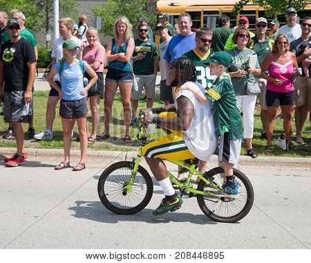 Green Bay WI - August 1 2017: Aaron Jones rides a young fans bike after football practice. The community owned Green Bay Packers have a long tradition of player involvement with fans.
