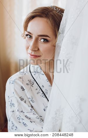 Beautiful Happy Blonde Bride In A Stylish Robe Posing Near Hanging Wedding Dress, Morning Wedding Pr