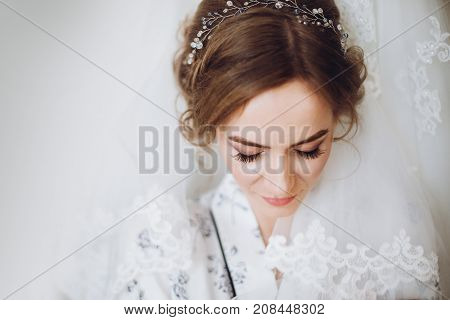 Beautiful Happy Bride Portrait, Smiling And Looking Down, Standing In Silk Robe At Her Luxury Weddin
