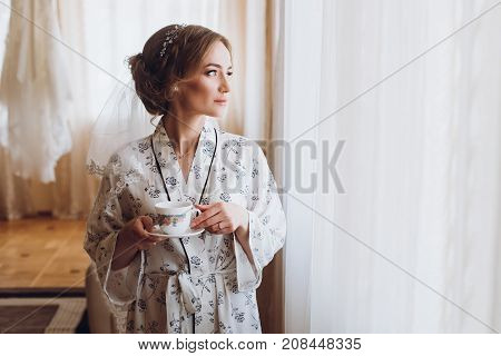 Gorgeous Bride In Elegant Robe Drinking Coffee In Luxury Hotel Room Near Window, Morning Before The