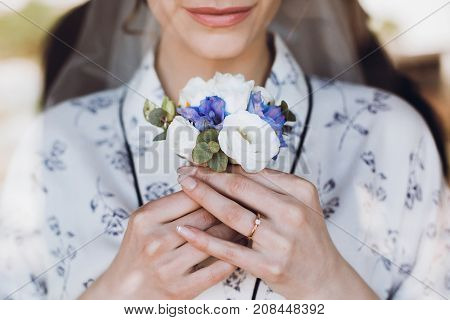 Beautiful Happy Bride Holding And Looking At Stylish Boutonniere By The Window, Standing In Silk Rob