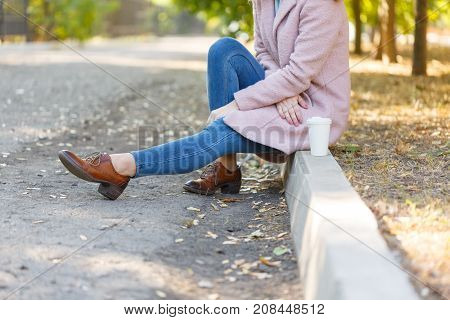 Girl in a pink coat. In brown shoes. Sits on the curb in the park. Concept - rest.