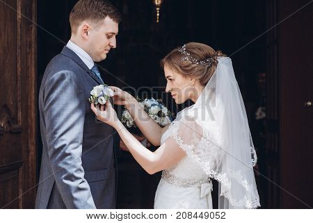 Romantic Wedding Moment, Beautiful Blonde Bride Putting On Boutonniere On Handsome Groom Near Church