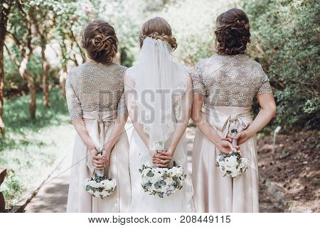 Bride With Bridesmaids Posing, Holding Bouquets At Back. Happy Wedding Bride With Girls Having Fun I