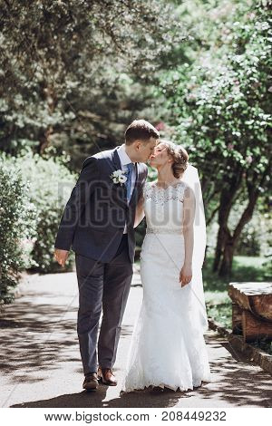 Cute Newlywed Couple Kiss In A Park,  Happy Bride And Groom Embracing Outdoors In Summer Garden, Bea