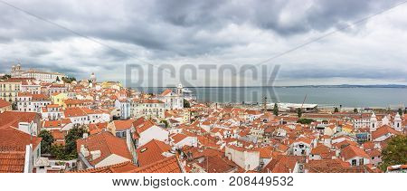 Lisbon Portugal - July 2017: Cityscape Architecture Panoramic Outdoor View of Portas do Sol viewpoint and famous Red Orange Roofs in Lisbon Portugal.