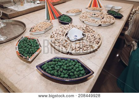 Pistachio And Salted Nuts On Tray On Beer Table At Wedding Reception In Restaurant. Luxury Catering.