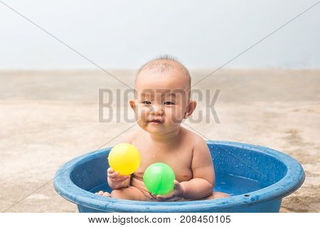 Cute New Born Baby playing ball in the plastic basin during showerchildren learning