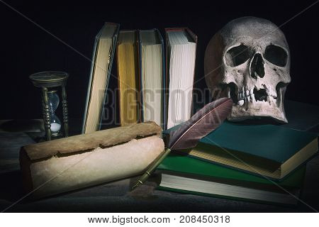 Literature concept. Old book with skull near scroll quill feather pen and vintage hourglass