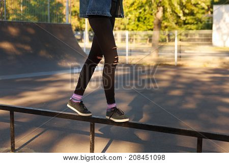 Female legs in ragged black jeans and black sneakers. Close-up. The girl is standing on a thin fence.
