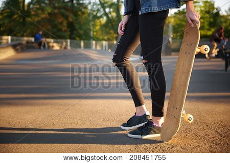 A girl in black ragged jeans holds a skate with her hand. In the park in the fresh air. Close-up.