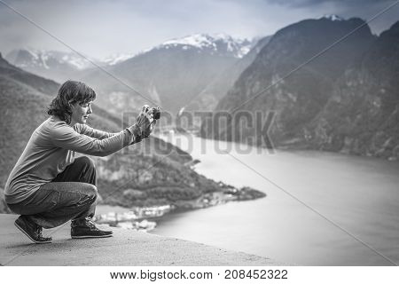Tourism and travel. Woman tourist taking photo with camera enjoying mountains fjords view in Sogn og Fjordane county. Norway Scandinavia black and white photo