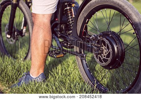 Man biker sitting on electric bike. Ebike bicycle environmentally friendly eco e-mountainbike transport. Healthy lifestyle
