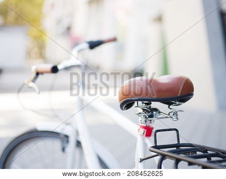 Close-up picture of a brown skin bicycle seat on a blurred urban background. Vintage, retro bike part. Old transportation. Copy space.