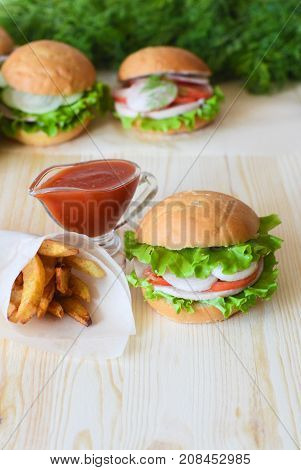 sandwiches with tomatoes and onions and lettuce and cucumbers next to a packet of French fries and next to the ketchup all on a wooden background background is blurred