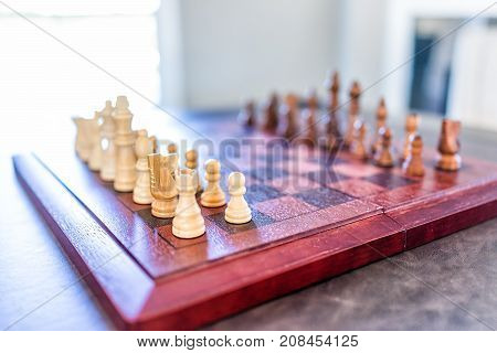 Closeup Of Chessboard With Wooden Pieces On Table In Sunlight