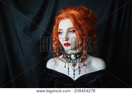 Seductive woman is a vampire with pale skin in a black dress and a necklace. Seductive girl witch with vampire claws and red lips. Gothic seductive model. Seductive outfit for halloween.