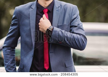 Successful manager in a dark business suit with a red tie against the background of a car. Stylish manager. Fashionable watch on manager hand. Manager correct a tie