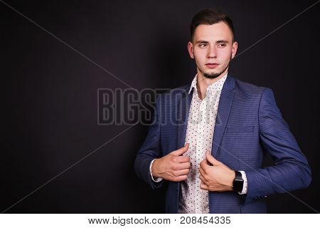 Successful young entrepreneur in business suit and white shirt and fashionable clock on hand. Stylish entrepreneur. Young entrepreneur on black background. Entrepreneur with a confident look