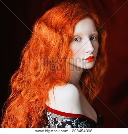 Red-haired unusual girl with curly hair with pale skin in a dressing-gown on a red background. Unusual model with red long hair. Redhead unusual girl with red lips. Unusual look
