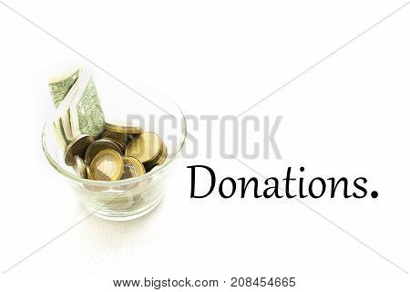 Glass jar with bills and coins inside and the word '' Donations '' written. On a white background.