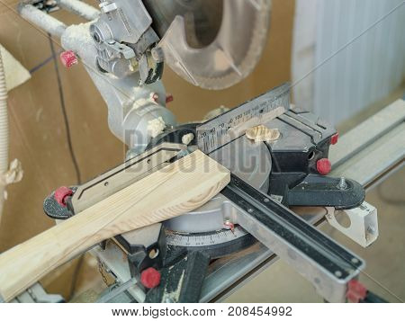 Gray machine circular saw, worker sawed the part to the desired size on a blurred background.