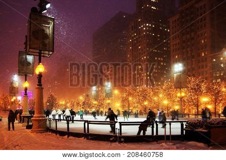 Snowy winter night background in light blur with falling snow and people in motion on a ice rink enjoying ice skating. Skyscrapers and trees decorated for holiday on a background.