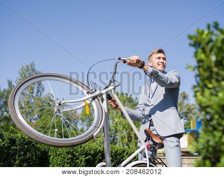 A young, handsome man in a gray suit raises his bicycle on the rack on the green garden of the administration