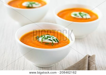 Fresh homemade cream of carrot soup with dollop of cream or yogurt and chives on top served in bowls photographed with natural light (Selective Focus Focus in the middle of the first soup)