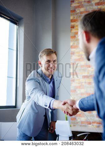 Men shaking hands. Confident businessman shaking hands with each other. Close-up of businessman's hand in office in formal attire.