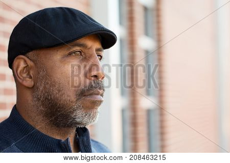 African American man standing alone looking sad.