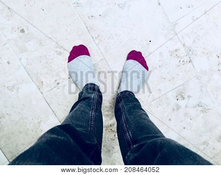 Man staying on the floor in grey and pink socks on his feet.