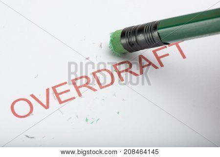 Pencil Erasing The Word 'overdraft' On Paper