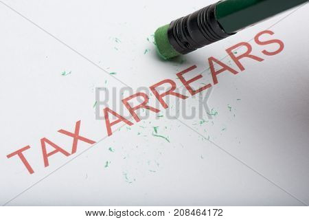 Pencil Erasing The Word 'tax Arrears' On Paper