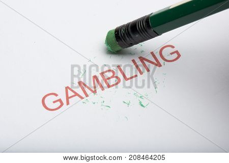 Pencil Erasing The Word 'gambling' On Paper