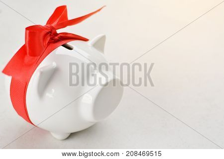 Piggy bank with red ribbon tape on white