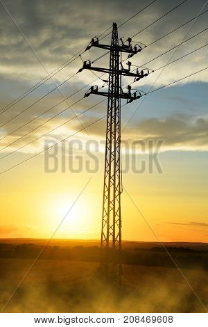 High voltage power pylon at sunset. Electricity distribution station.