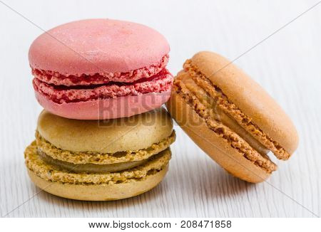 some delicious macaroon on white wooden background