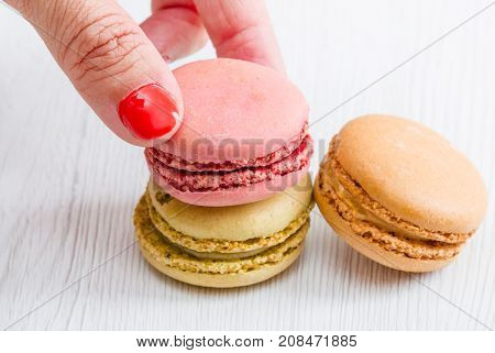 a woman hand takes a macaroon on wood table